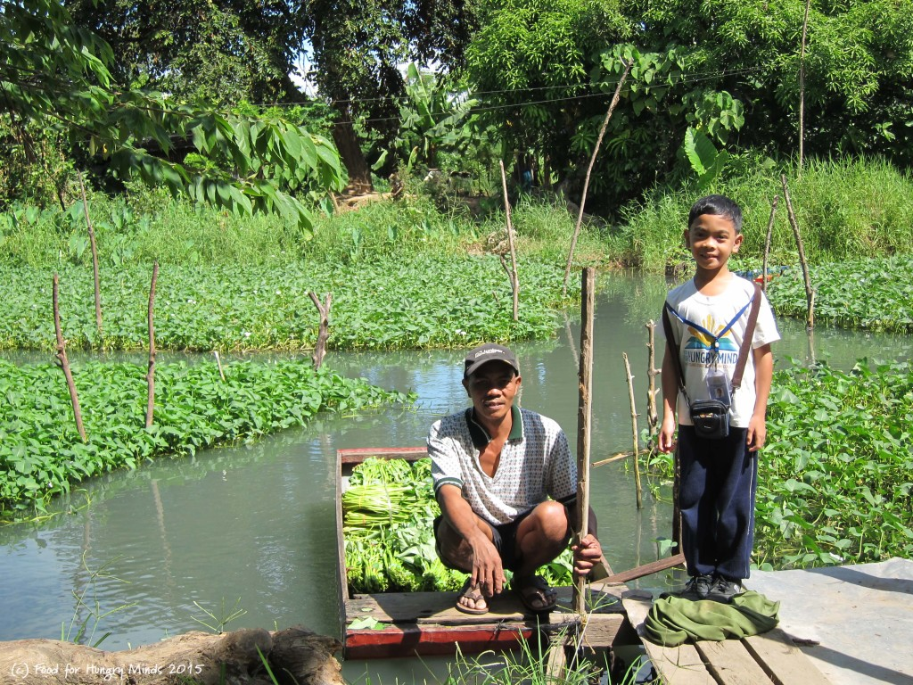 Tatay Bomalay with his son, Elmark, at the small river where he gets Kangkong to sell to a market trader